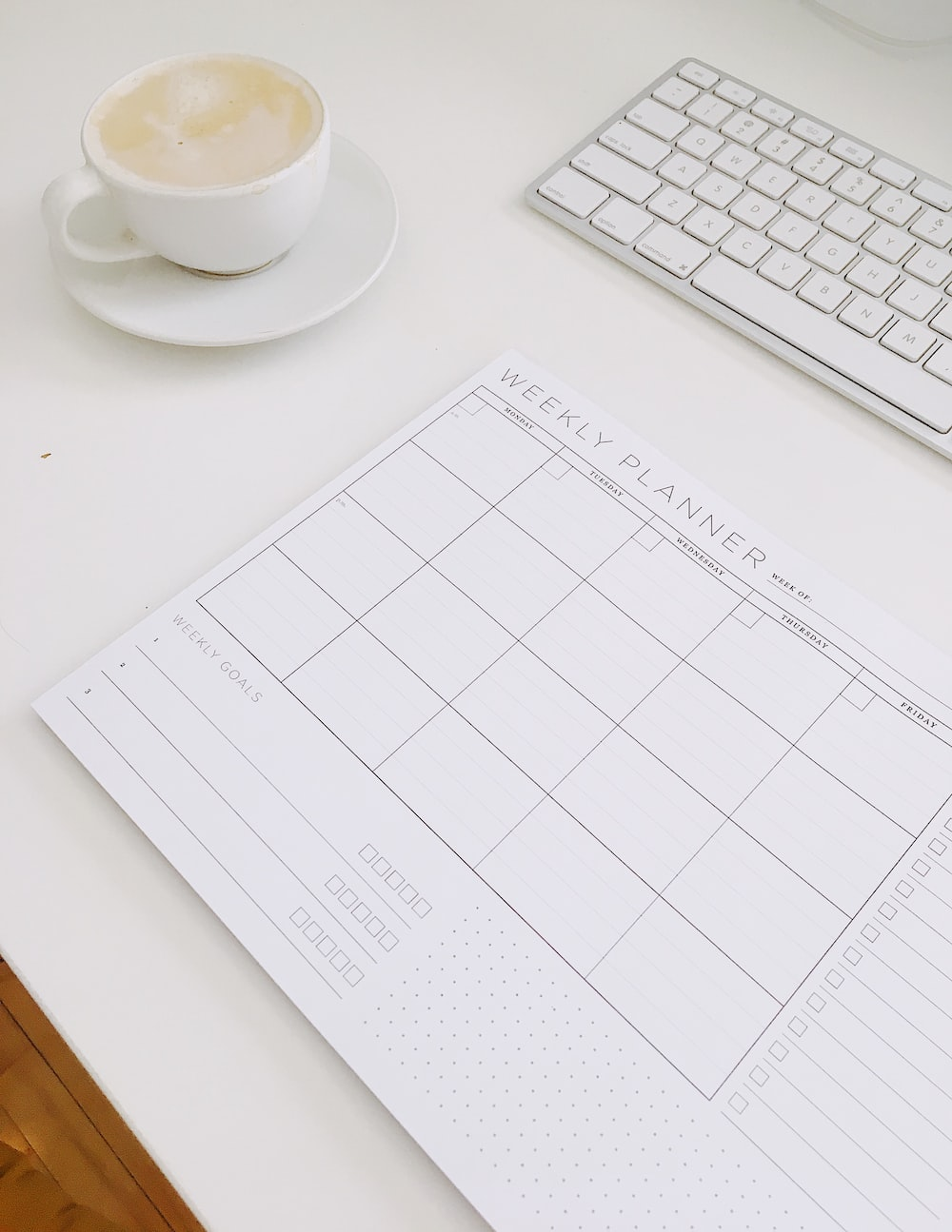 cup of cappuccino near weekly planner