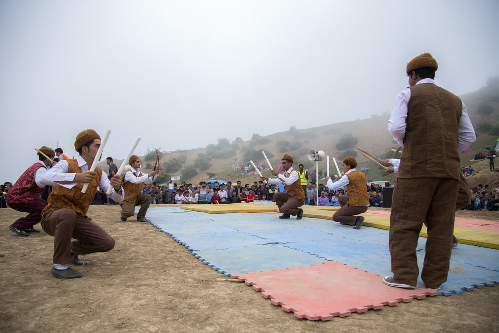 several men holding sticks while squatting in puzzle mat