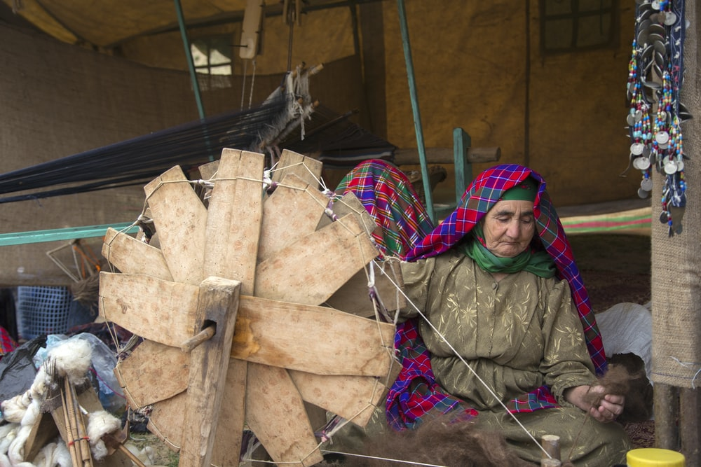 woman sitting beside brown fan