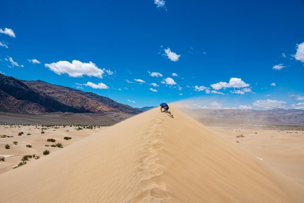 man walking on sand dunes