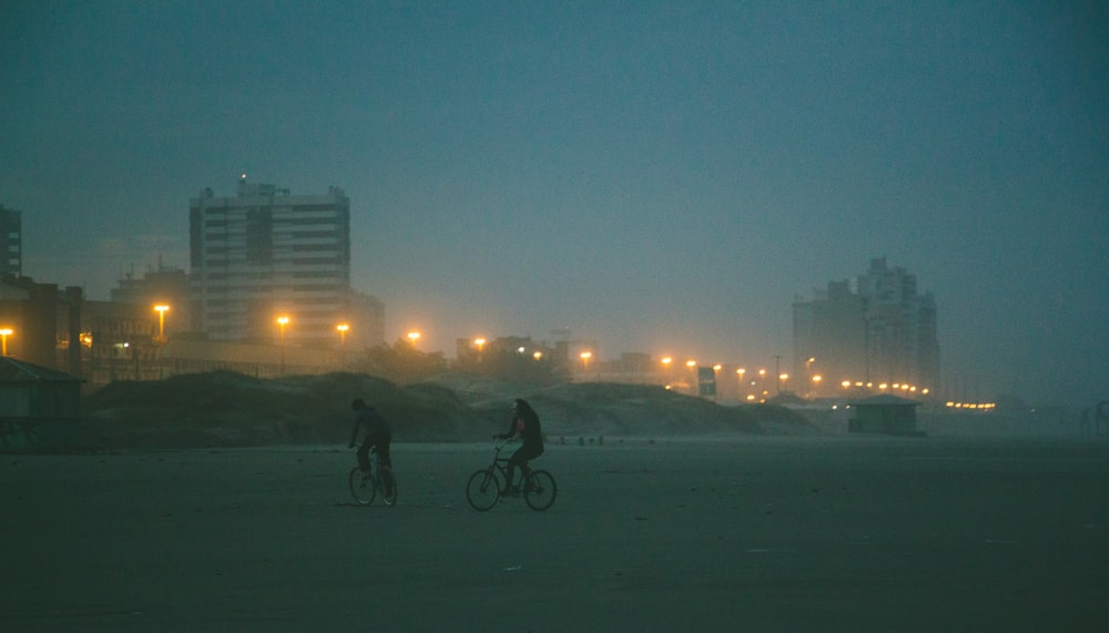 two people biking on snow field viewing high-rise buildings during night time