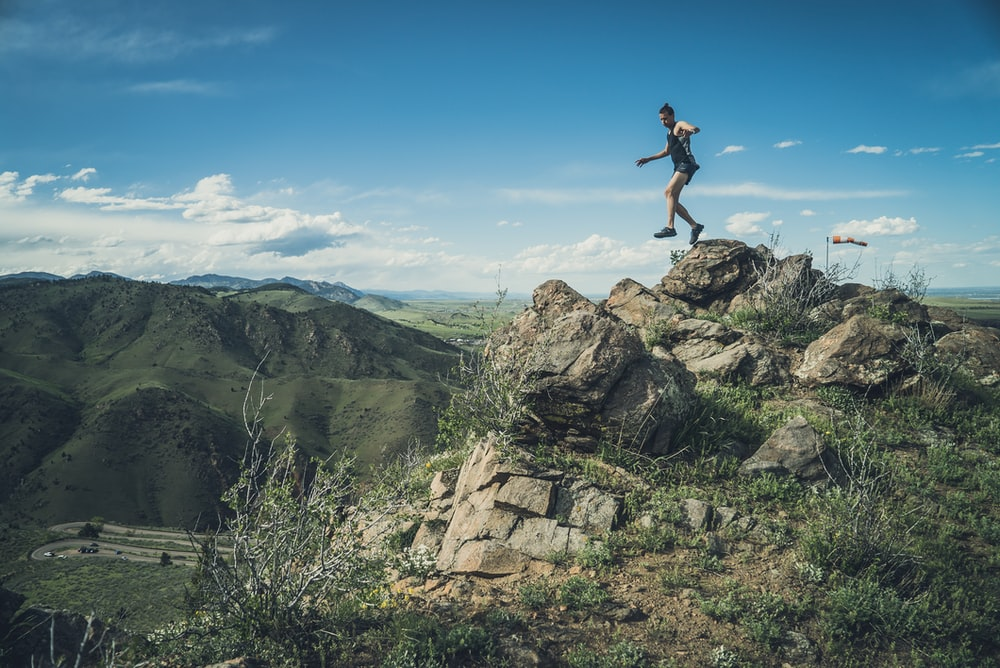 man jumping from a rock on mountain during day