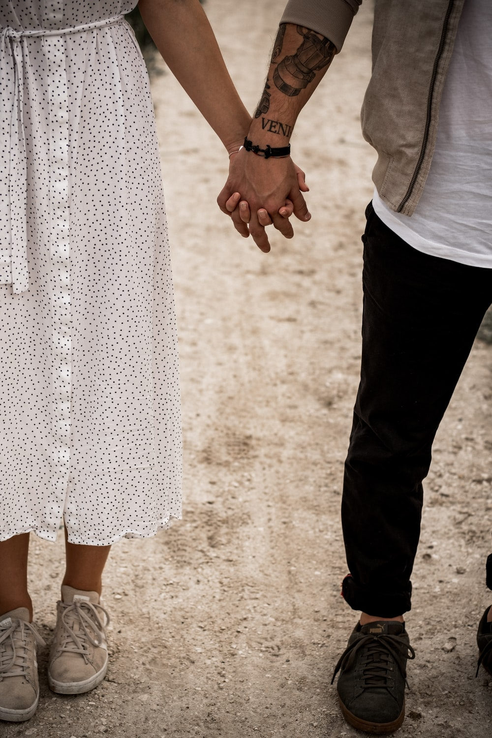 man and woman standing and holding hands together