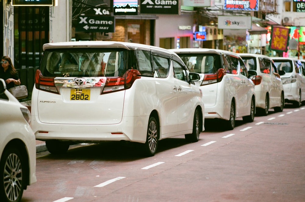 four white Toyota station wagons lined on road