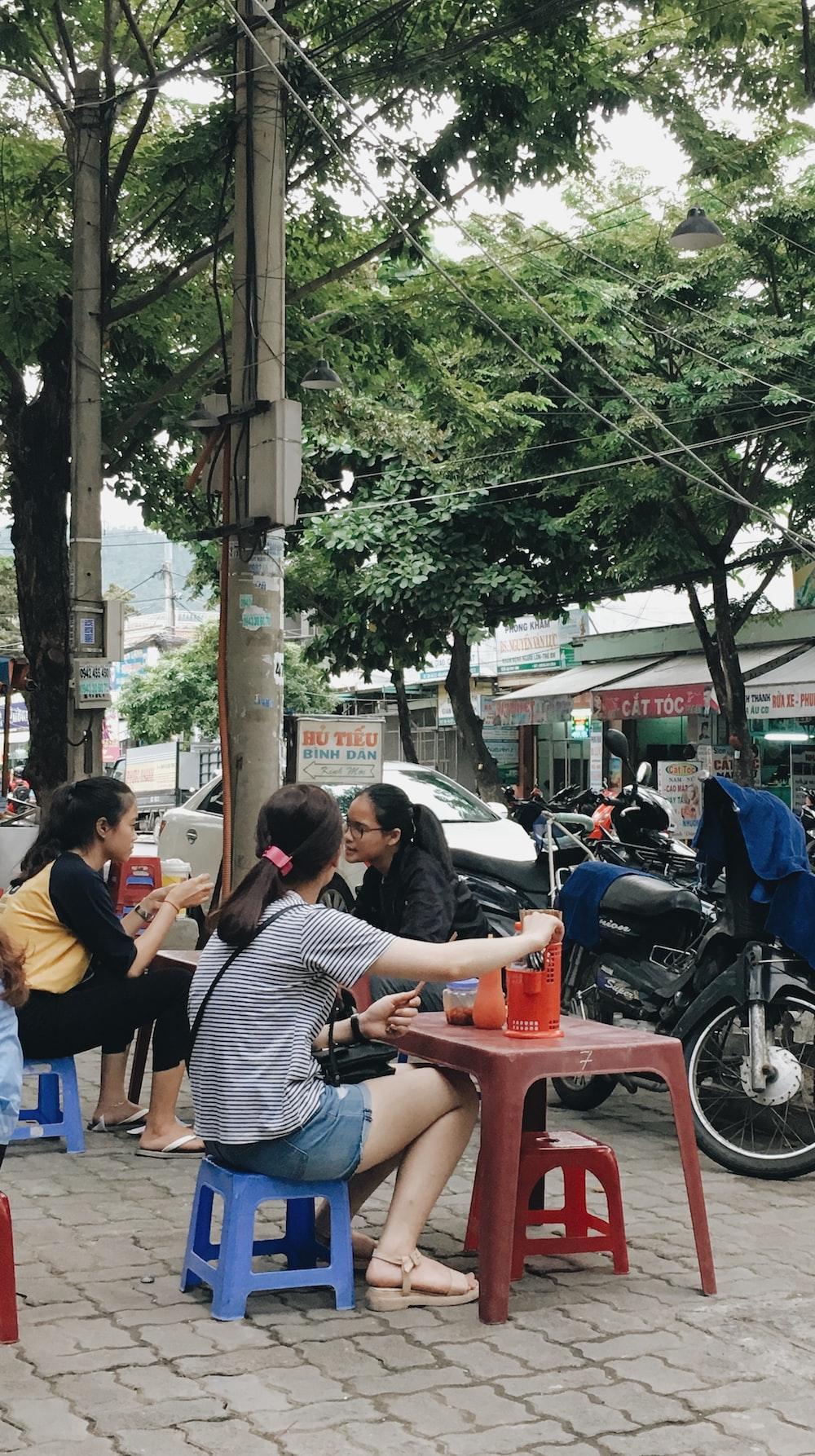 three women sitting near parked black motorcycle