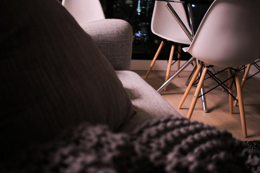 vacant white armless chair near gray sofa