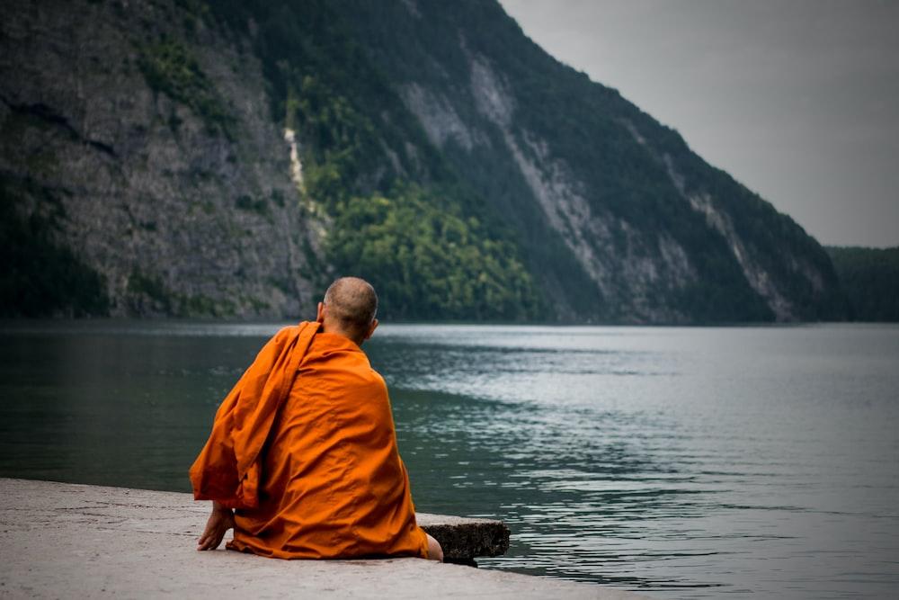 man sitting near ocean