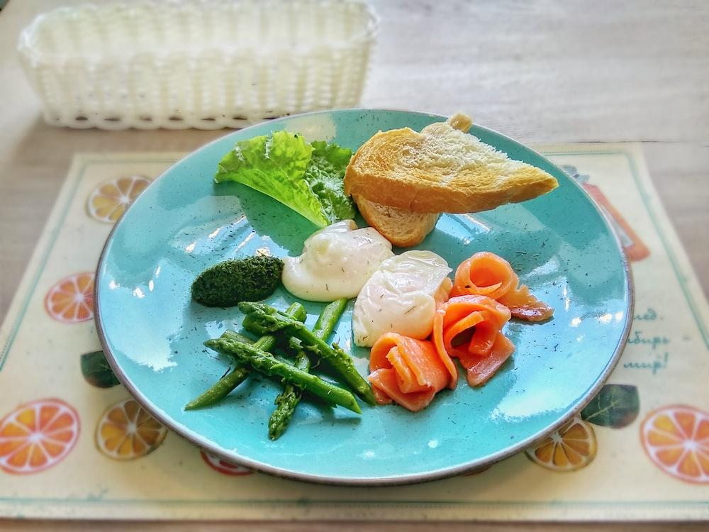sliced bread near lettuce, asparagus, salmon, and cream on ceramic plate