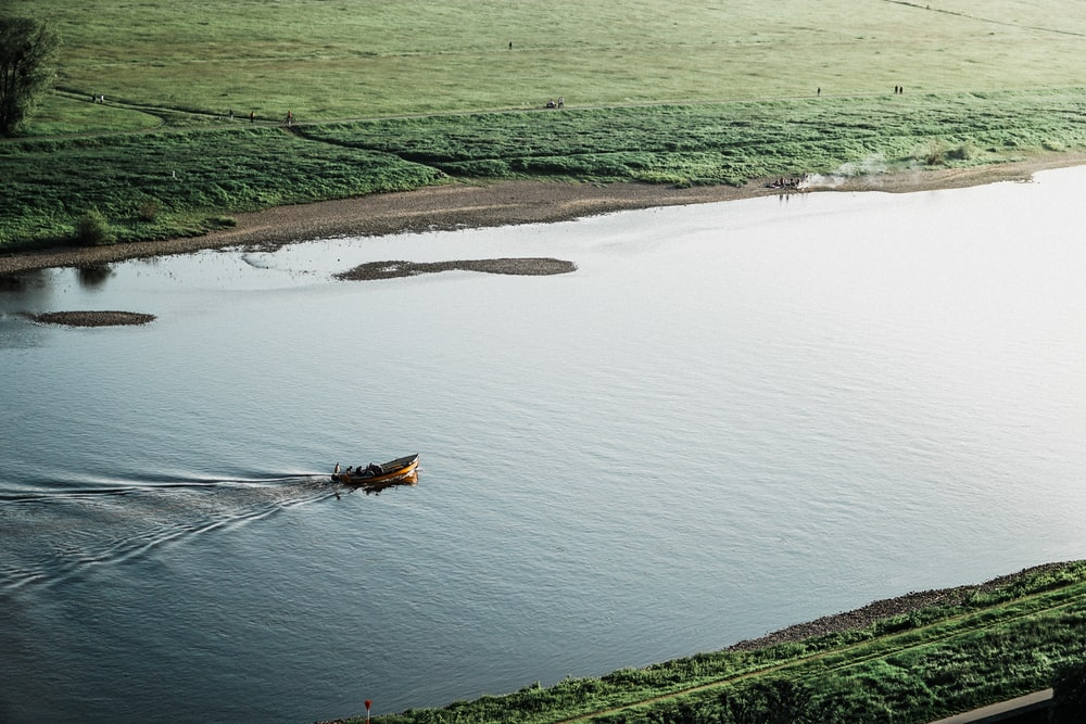 brown boat on river surrounded by green grass