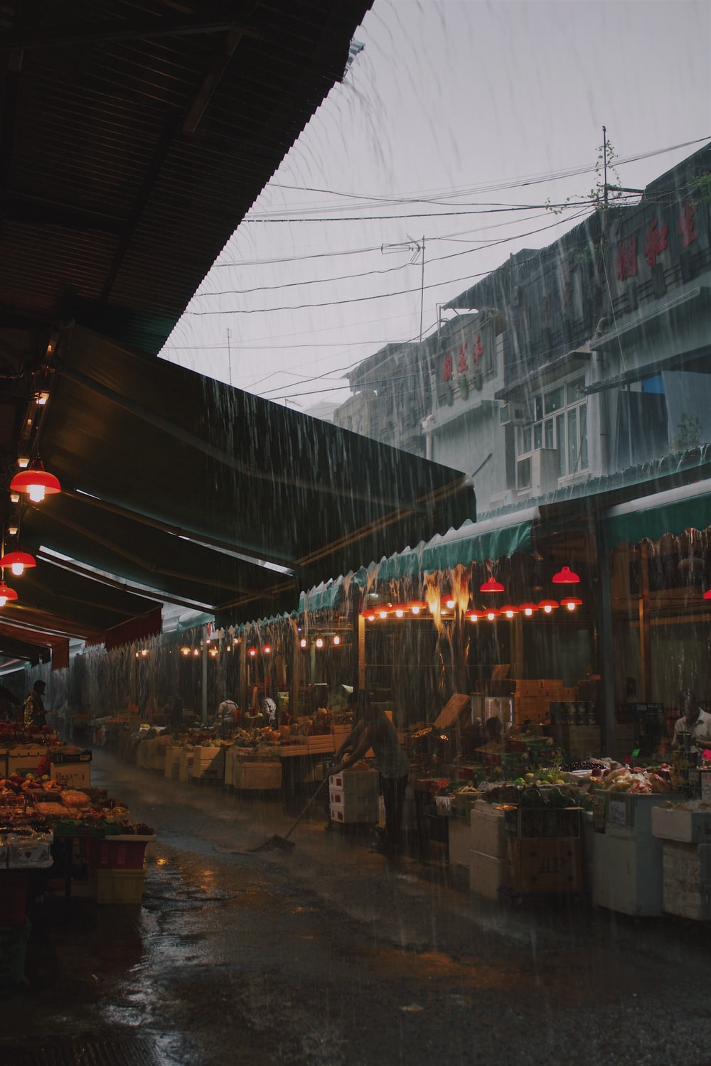 people in the market near different goods on display during rainy season