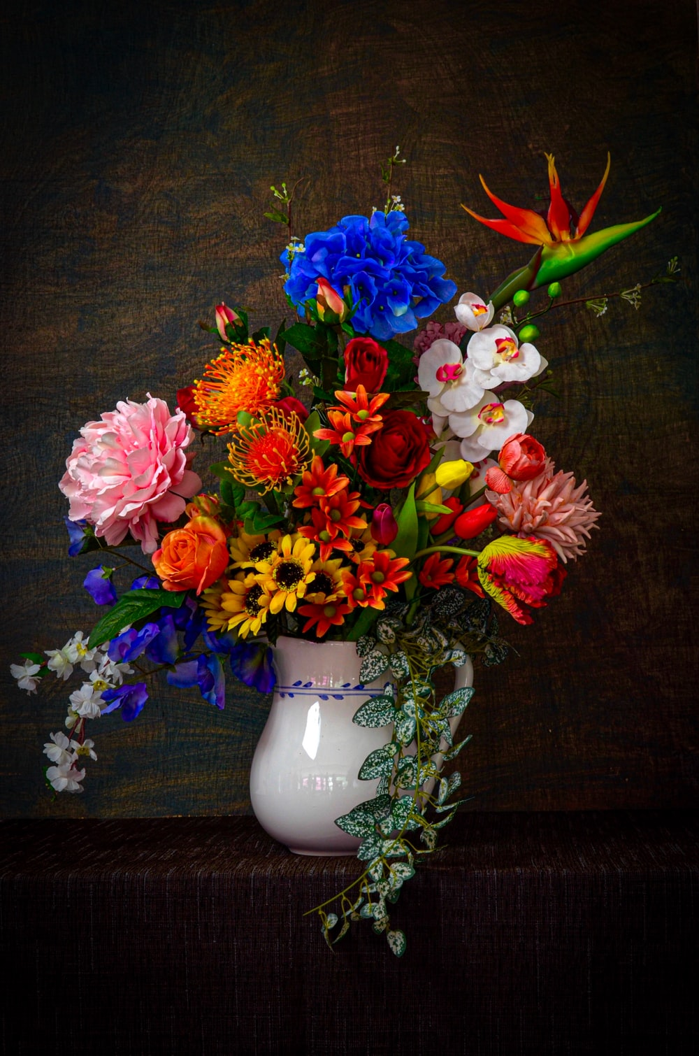 assorted flowers in white vase on brown surface