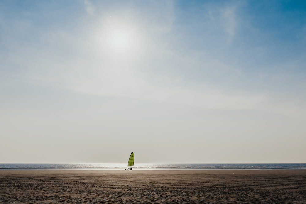 green sailboat on sea during daytime