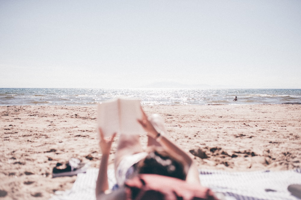 person lying on blanket while reading on beach