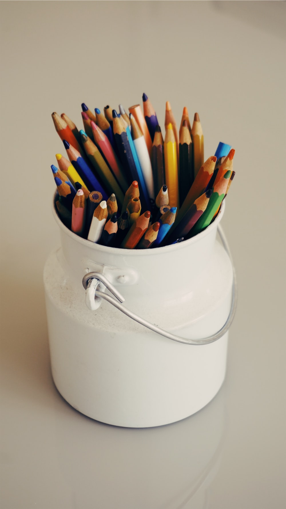 assorted-color coloring pens on white bucket