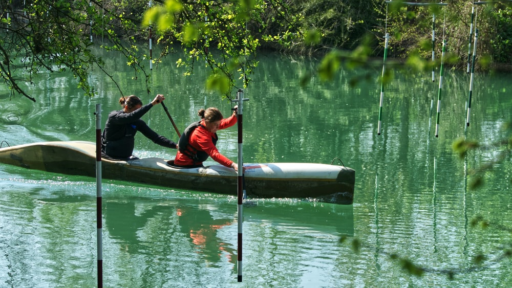 two women riding on black and gray kayak