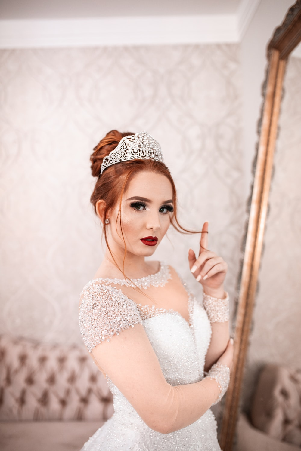 woman in white wedding gown facing the mirror