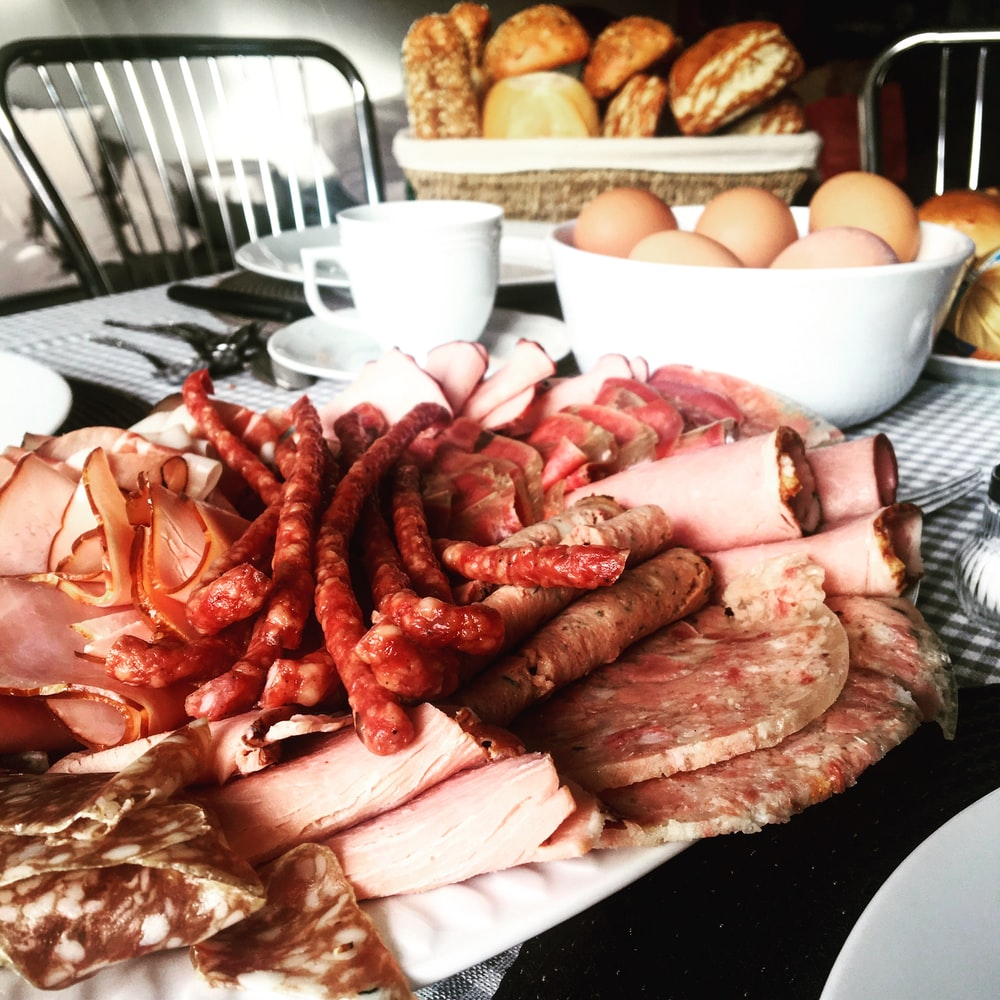 sausages near sliced ham beside chicken eggs in bowl on table