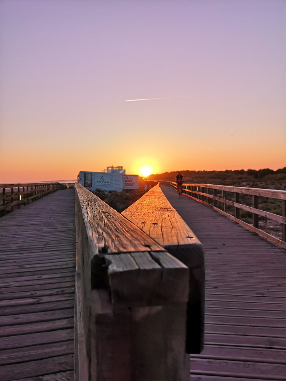 brown wooden pathway during sunrise