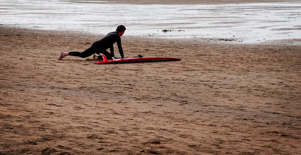 man in black wet suit on red surfboard on shore