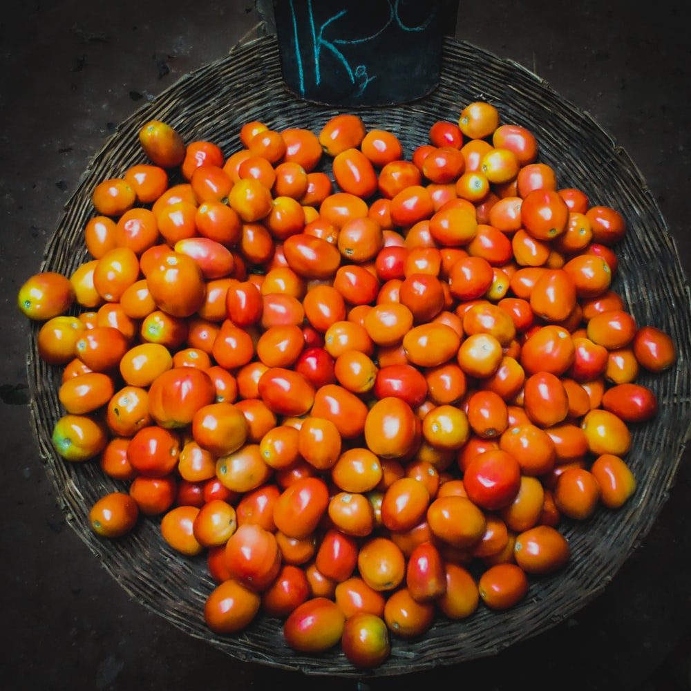 orange and red tomatoes on basket