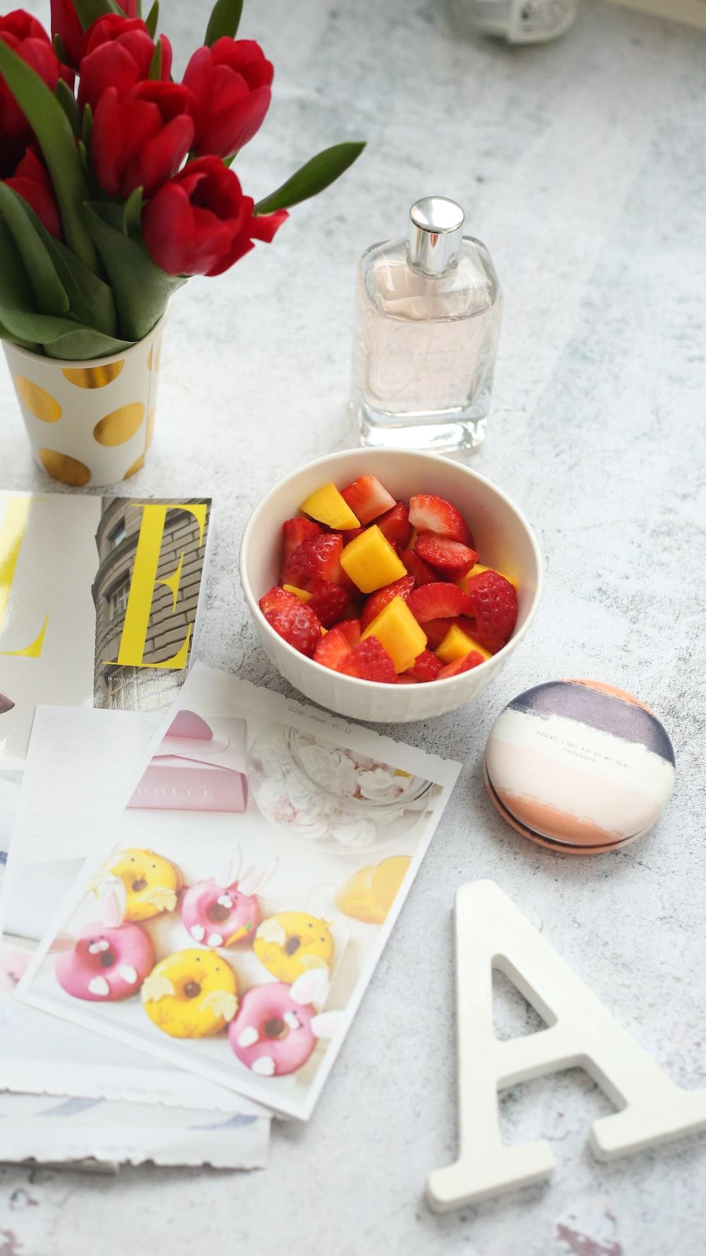 sliced strawberries on bowl beside clear glass bottle