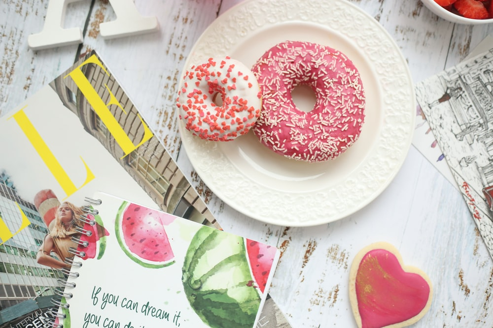 flat lay photography of two strawberry doughnuts
