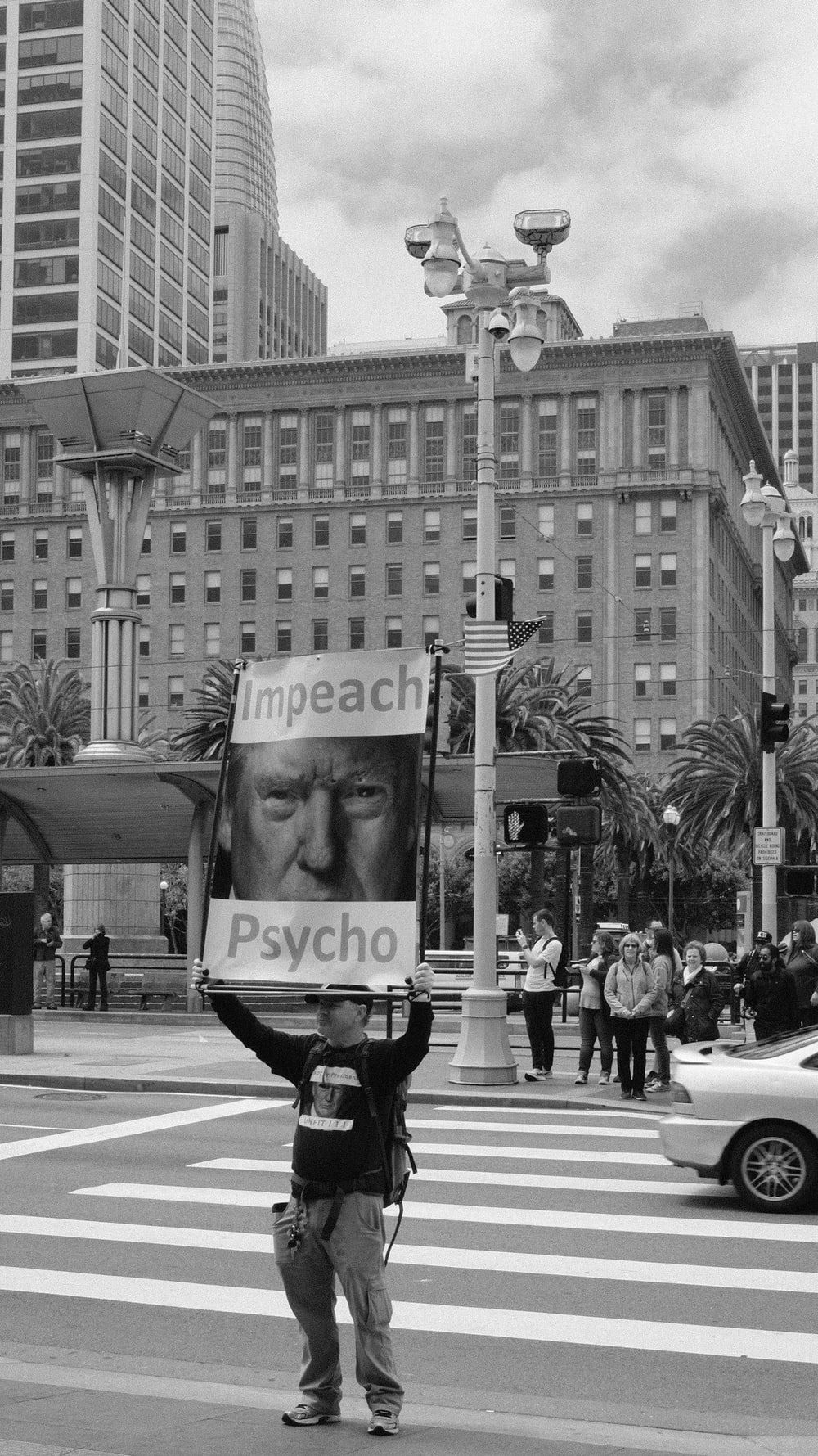 greyscale photography of man standing on road holding psycho banner
