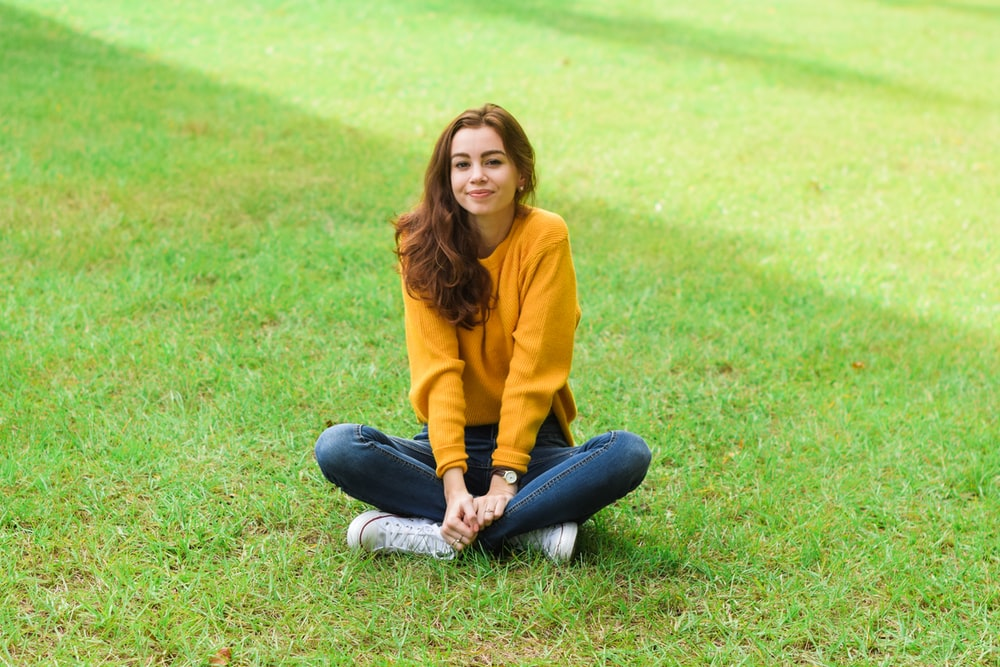 woman sitting on green grass