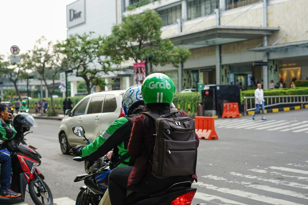 """Grab Bike Driver picking up passenger. Grab is a technology company that offers wide range of ride-hailing and logistics services through its app in Southeast"""