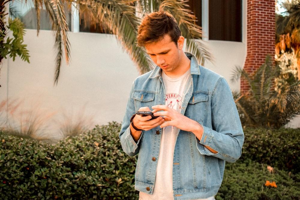 man in blue denim jacket using phone