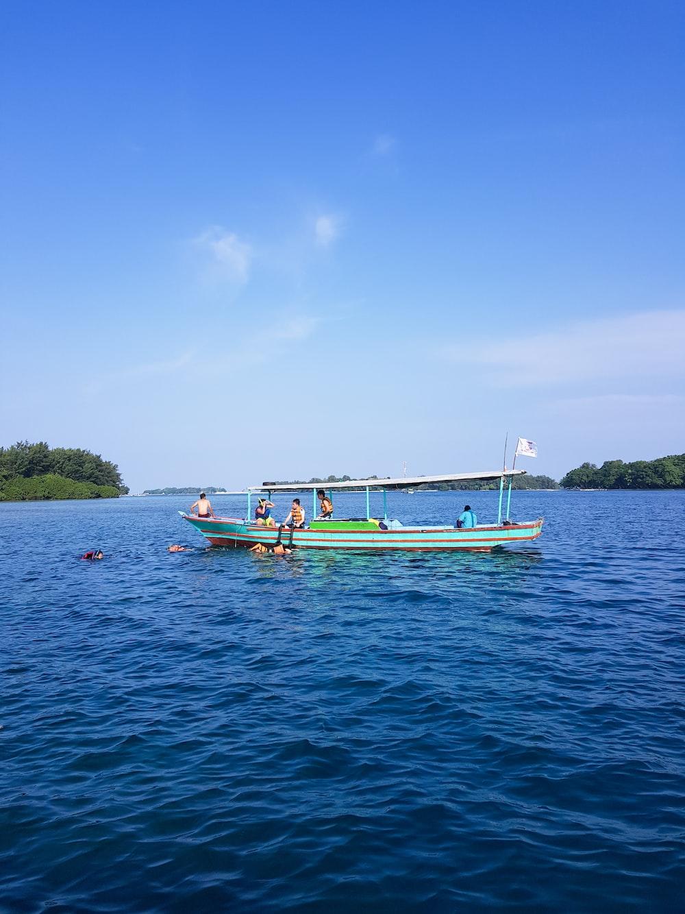 people swimming near boat