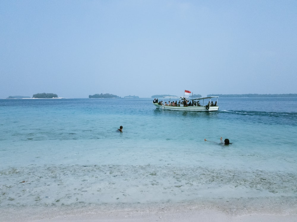 people swimming on sea near boat