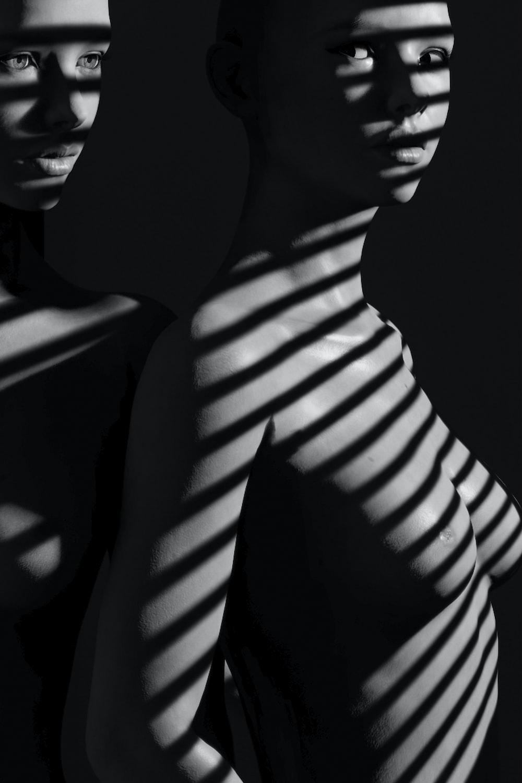 grayscale photo of naked woman on window panel