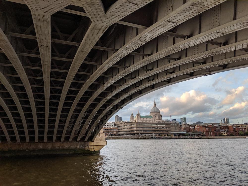 grey concrete buildings near body of water through bridge