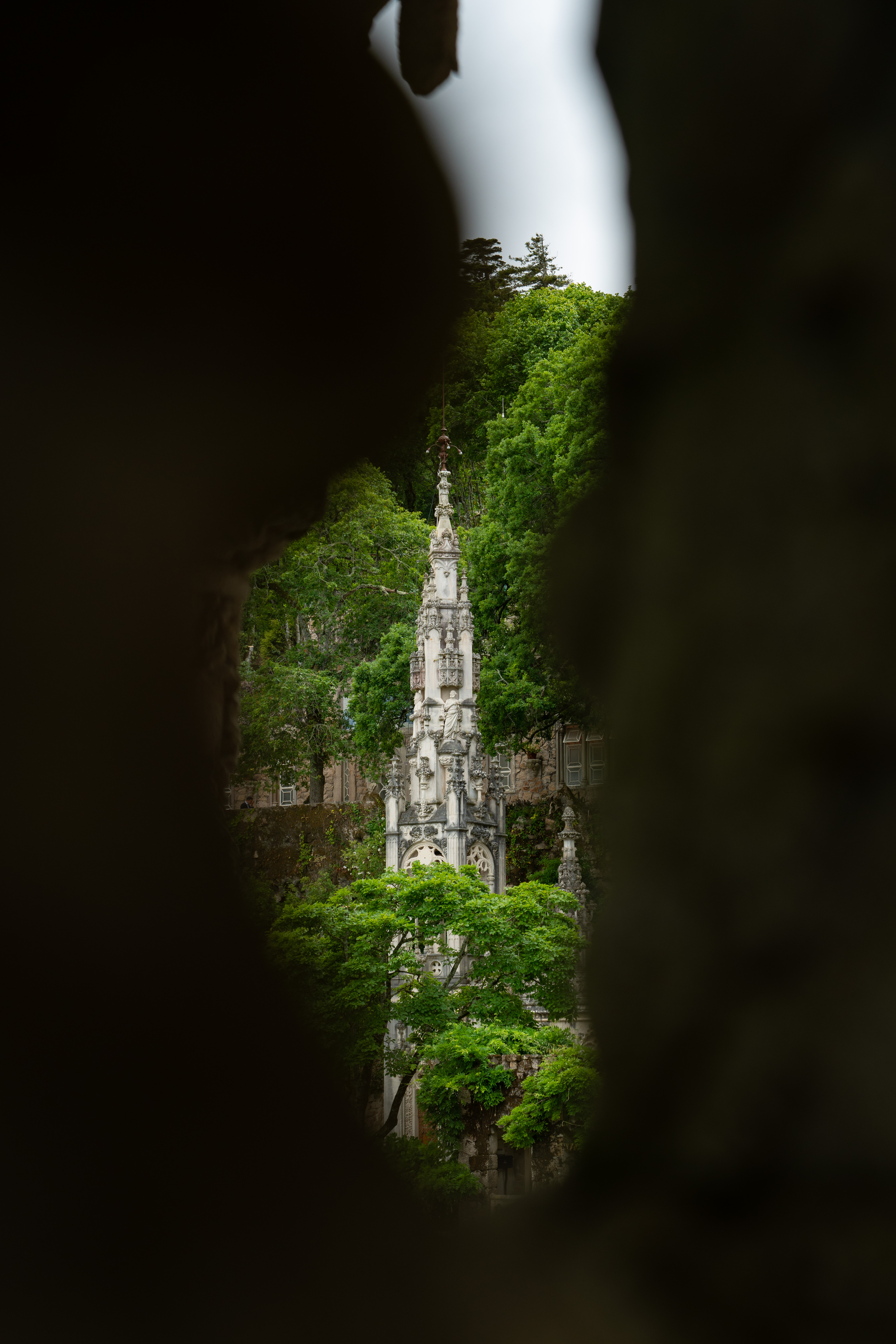 A spire at Quinta da Regaleira in Sintra, viewed through a gap between other stone carvings. The grounds mix forest, garden, and architecture seamlessly.