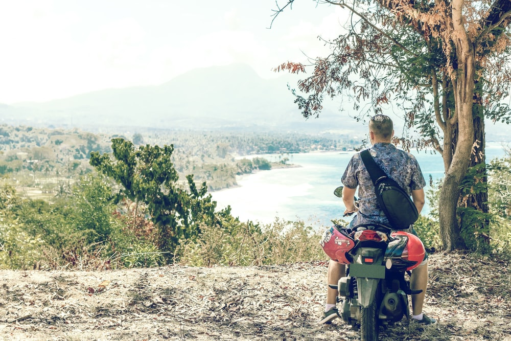 man facing the ocean and island on motorcycle near tree