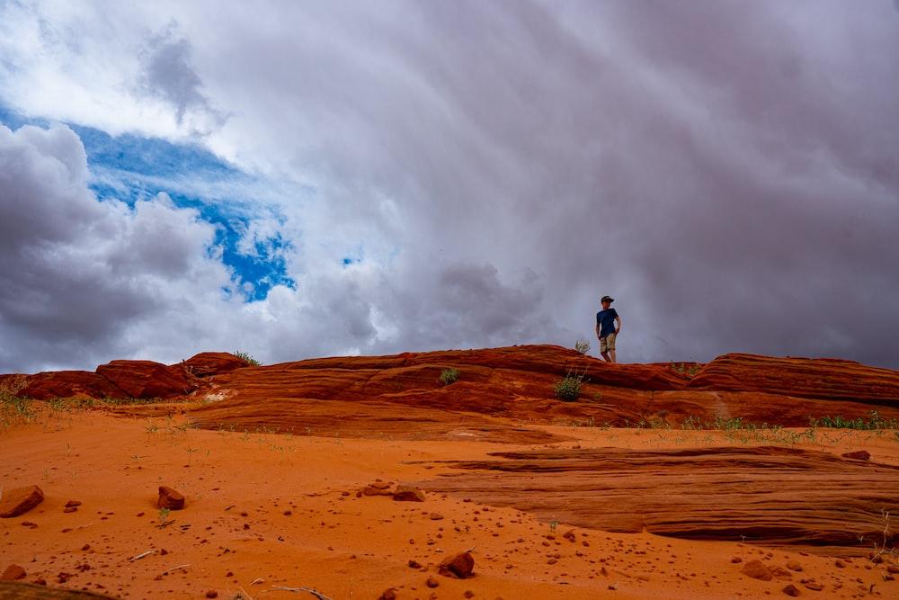 man standing on brown field