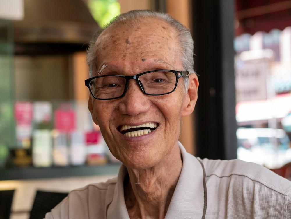 smiling man wearing eyeglasses inside room