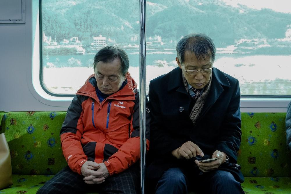 two men sitting inside passenger vehicle