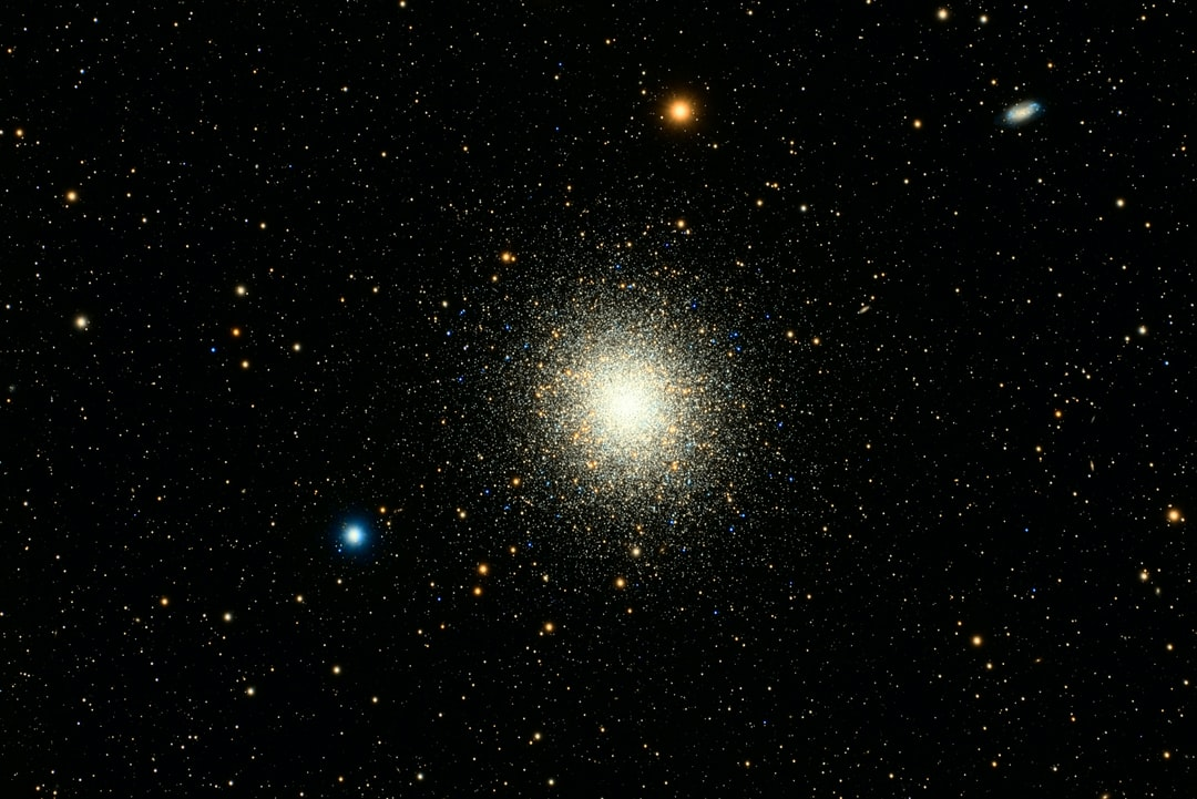"""Messier 13 – the Great Globular Cluster in Hercules  Located in the armpit of the constellation Hercules, M13 is one of the best known globular clusters in the northern hemisphere. Discovered by Edmond Halley (for whom the comet is named) in 1714 and cataloged by Charles Messier in 1764, it's a cluster of several hundred thousand closely grouped stars. The stars are about 100 times more densely packed than in our area of the galaxy. It's estimated to be approximately 22.2 thousand light years away, with a diameter of 145 light years. The galaxy in the upper right is NGC 6207, which is about 30 million light years away and 34,000 light years across.  Globular clusters reside in the halo of a galaxy as opposed to the disk and are bound together by gravitational forces. There are about 150 known globular clusters in the Milky Way, with an estimated 20 more hidden by dust lanes. They are generally comprised of very old stars, and M13 is estimated to be 11.65 billion years old. The process in which globular clusters are created is largely unknown, but it's hypothesized that they originate from areas of starburst activity and interactions between galaxies. There is no known active star formation in any of theses clusters, but due to the proximity of the stars collisions occur, and new stars are created. These new stars are called """"blue stragglers"""", some of which may be seen in the photo. The proximity of the stars (on average about one light year apart) also creates many binary star systems (think Tatooine), but due to the age and makeup of the stars there are very few with planets.  This is about 3:15 hours of exposure."""