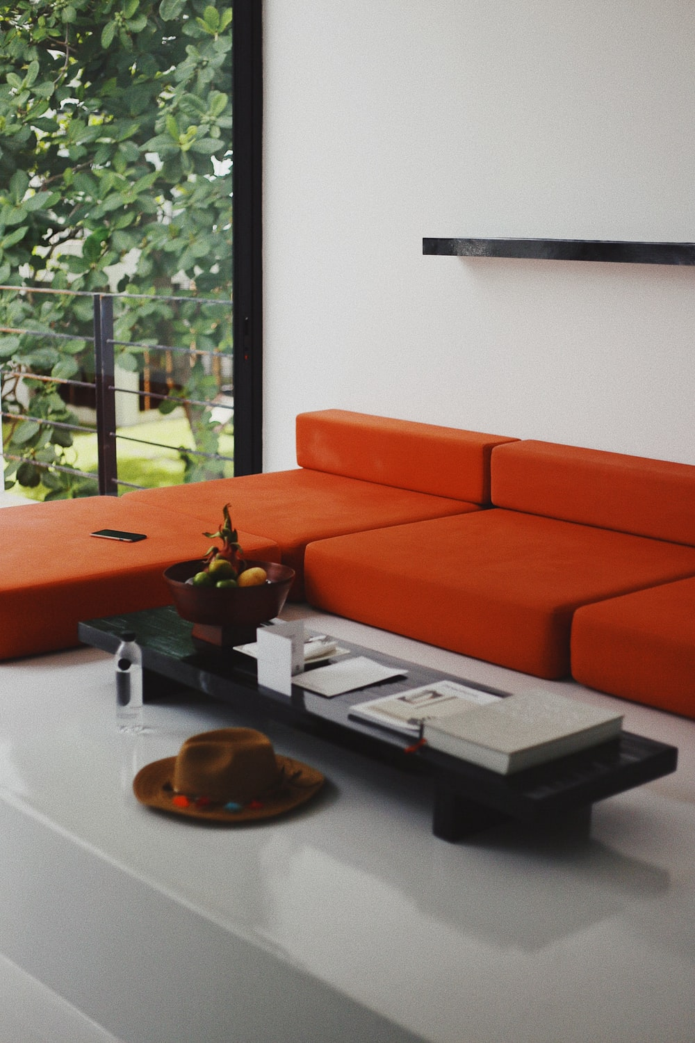 coffee table in front of orange fabric sectional sofa