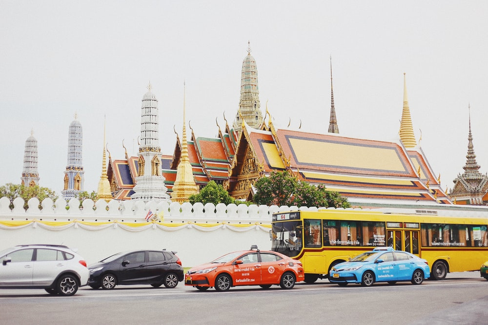 assorted-color vehicles parked near wall during daytime