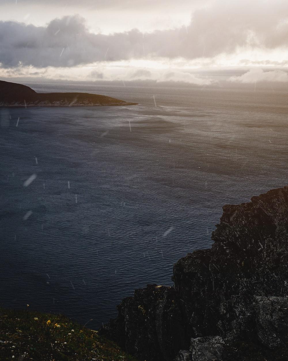 beach cliff viewing calm sea under gray skies