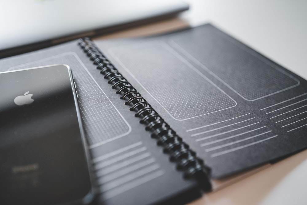 black iPhone on black spiral notebook