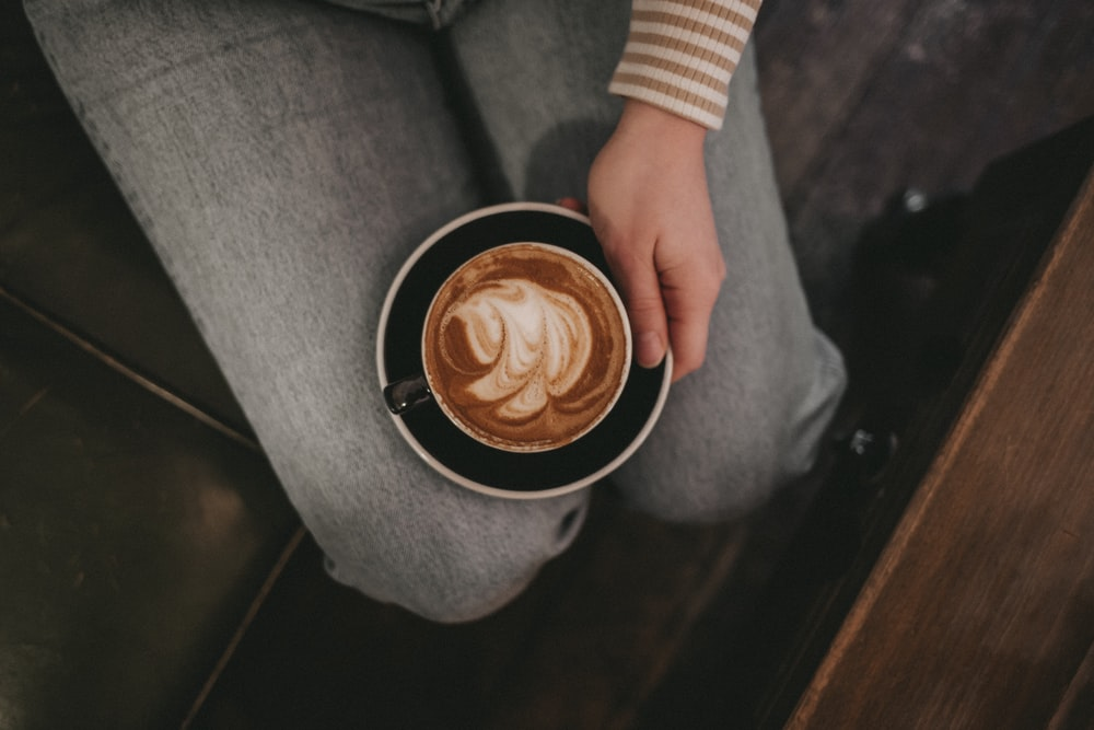 sitting person holding black saucer with white cappucino mug