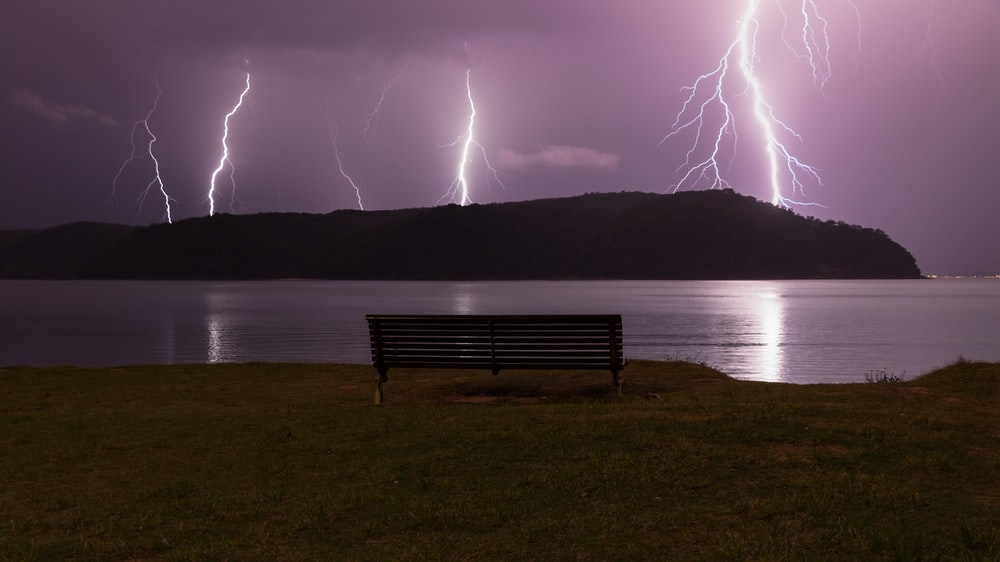 brown bench front of body of water with thunder storm