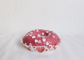 cupcake with heart toppings on white surface