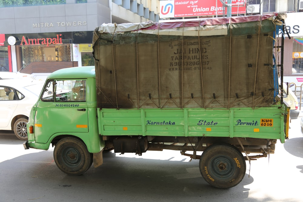 green and brown drop-side truck near gray building