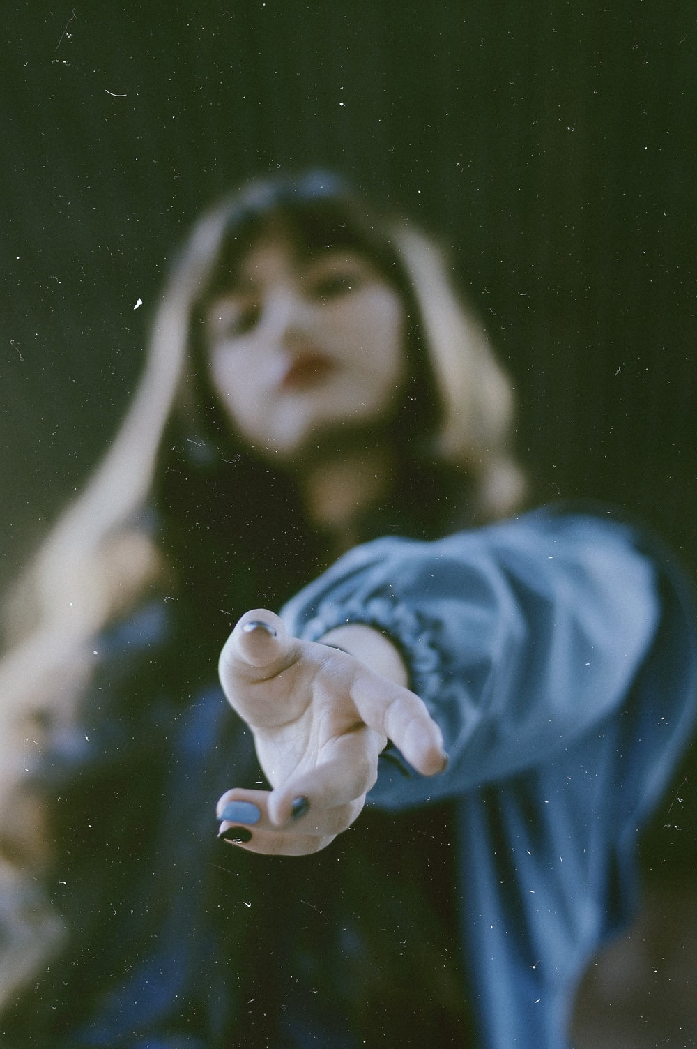 woman in blue jacket reaching out using left hand