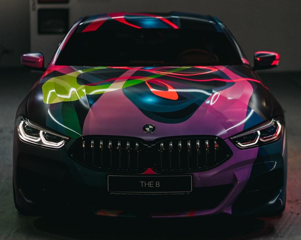 black and multicolored BMW car parked on gray floor